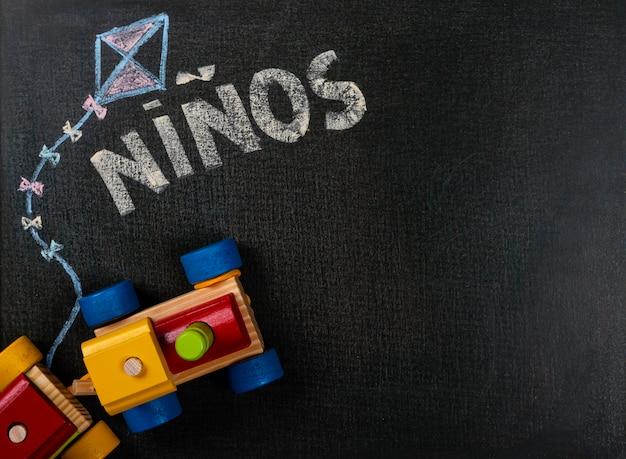 Dessin sur du papier de verre. niños (espagnol) écrit sur un tableau et un train en bois. espace de copie de fond. Photo Premium