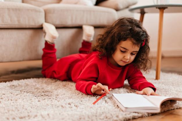 Dessin D'enfant Concentré Dans Le Cahier. Tir Intérieur D'un Enfant Mignon Allongé Sur Un Tapis Avec Un Stylo. Photo gratuit