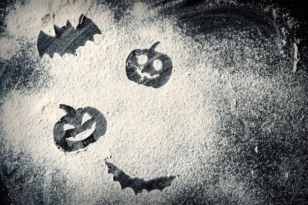 Dessin lanterne citrouille halloween et bat sur fond de farine de blé Photo Premium