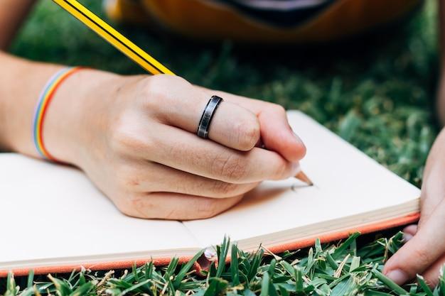 Un Dessin à La Main Avec Un Crayon Sur Un Ordinateur Portable Sur L'herbe. Photo Premium