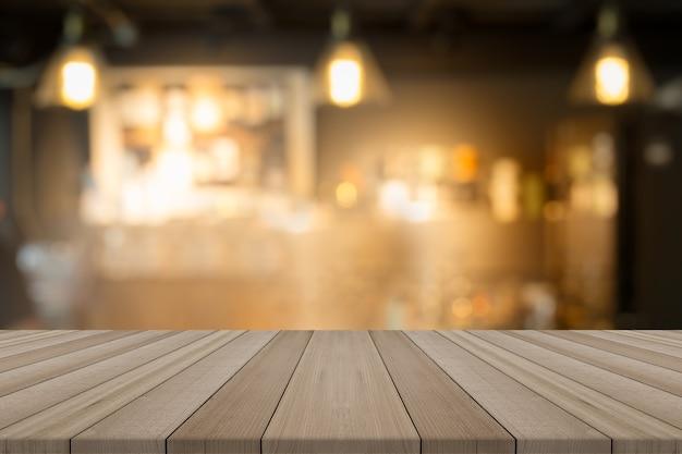 Dessus de table en bois vide sur café de forme de fond flou, pour le montage de vos produits Photo Premium