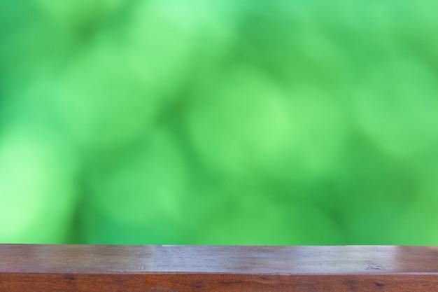 Dessus de table en bois vide sur fond abstrait bokeh vert flou Photo Premium