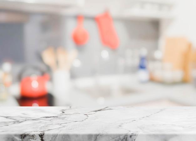 Dessus de table en pierre blanche et fond d'intérieur de cuisine floue - peut utilisé pour l'affichage ou le montage de vos produits. Photo Premium