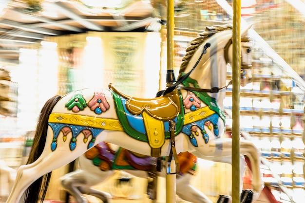 Détail de cheval nostalgique du carrousel en rotation avec des flous de lumière la nuit Photo gratuit