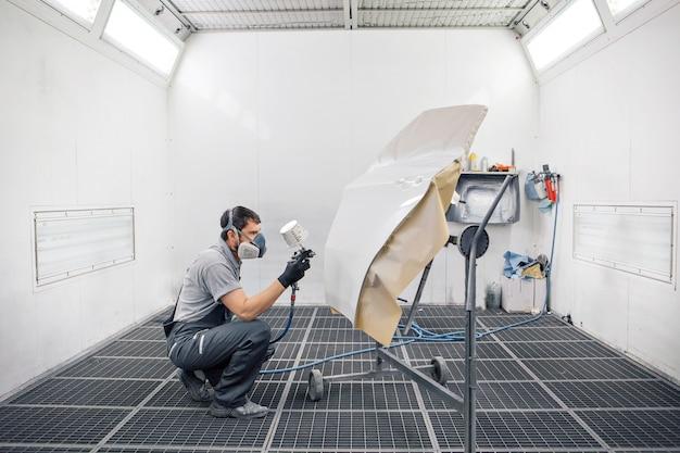 Détail du gros plan de la machine. la peinture est appliquée sur la surface de la machine Photo Premium