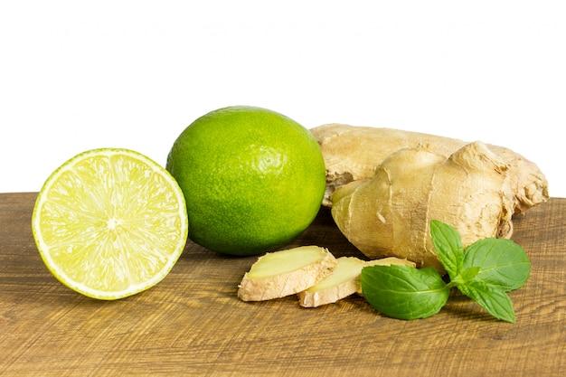 Détail de gingembre frais entier et coupé au citron vert Photo Premium