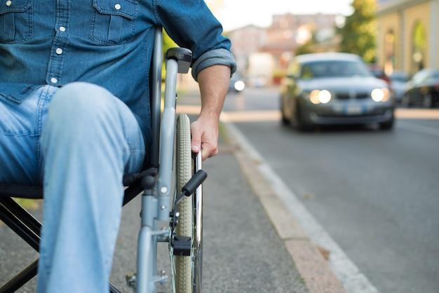 Détail d'un homme en fauteuil roulant dans une rue urbaine Photo Premium