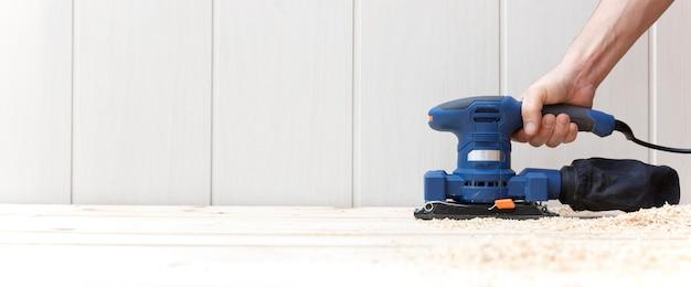Détail De La Personne Travaillant Avec Une Ponceuse électrique Sur Le Plancher En Bois Naturel De Sa Maison. Photo Premium