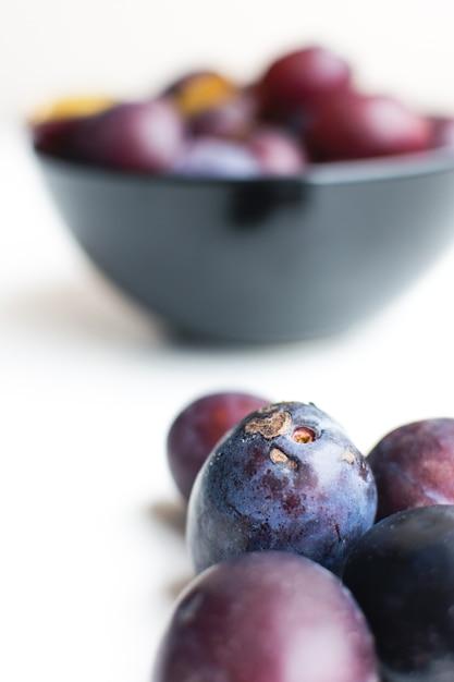 Détail de prunes organiques fraîches sur fond blanc Photo gratuit