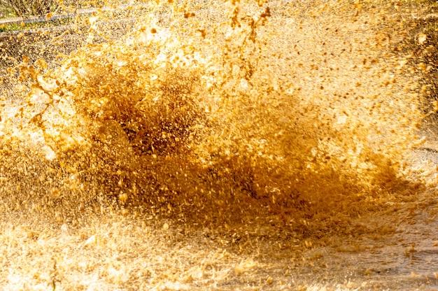 Détails des gouttes d'eau et de la boue d'une éclaboussure dans une flaque d'eau dans une course d'obstacles. Photo Premium