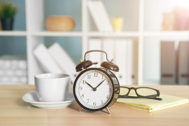 Détails intérieurs de bureau avec réveil et articles de papeterie Photo Premium