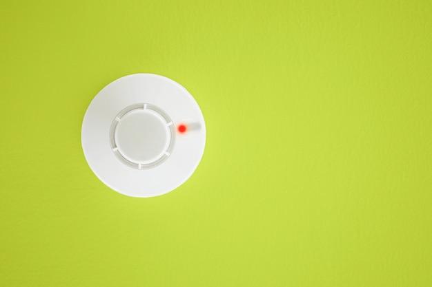 Détecteur de fumée sur fond jaune. système de sécurité. Photo Premium