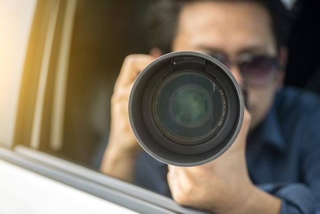Détective privé assis à l'intérieur de la caméra de voiture avec appareil photo reflex Photo Premium