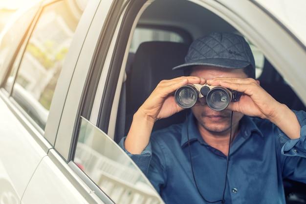 Détective privé assis à l'intérieur de la voiture de photographie avec appareil photo reflex Photo Premium