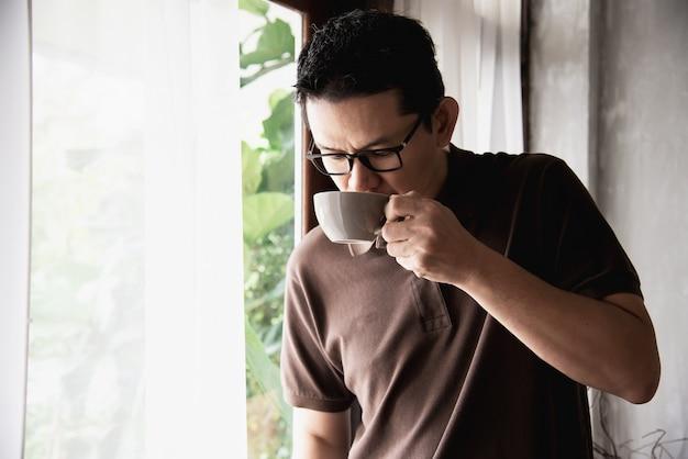 Détendez-vous homme asiatique en buvant un café Photo gratuit