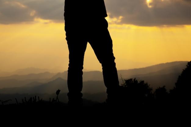 Détendez-vous l'homme sur la colline à la silhouette du coucher du soleil. Photo gratuit