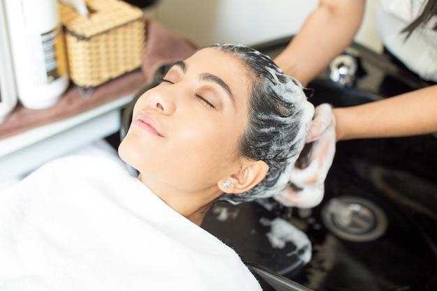 Détendue jeune femme en train de se laver dans le salon Photo gratuit