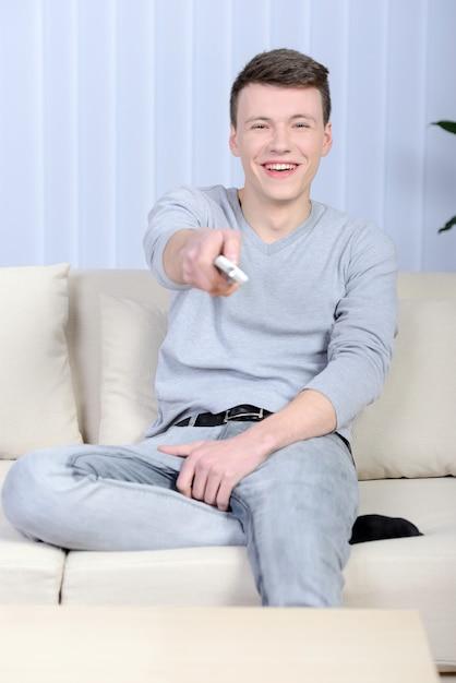 Détendue Jeune Homme Devant La Télé à La Maison Dans Le Salon Lumineux Photo Premium