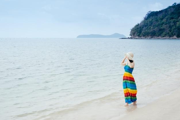 Détente femme sur le ciel de la plage et des nuages. Photo Premium