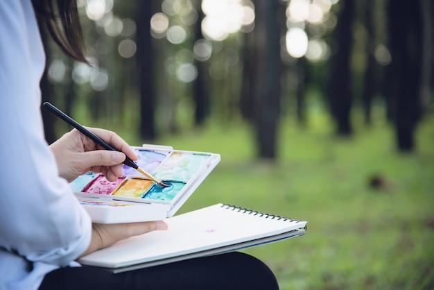 Détente femme peinture aquarelle oeuvre dans la nature verte forêt de jardin Photo gratuit