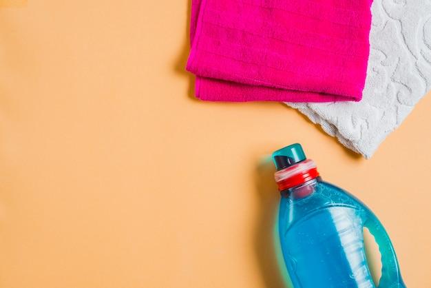 Détergent à lessive avec deux serviettes sur fond coloré Photo gratuit