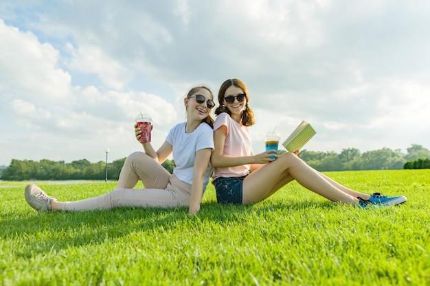 Deux adolescentes copines sont assises sur une pelouse verte Photo Premium