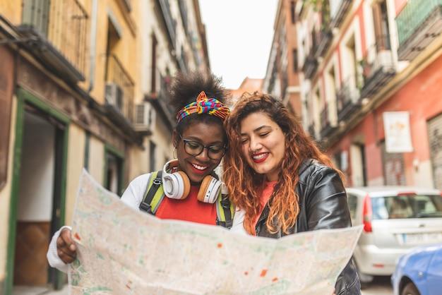 Deux adolescentes latines utilisant une carte et voyageant ensemble. Photo Premium