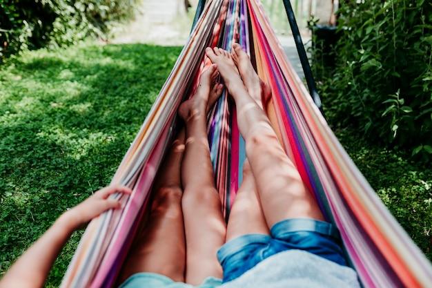 Deux Adolescentes Méconnaissables Allongées Sur Un Hamac Coloré Dans Le Jardin. Se Détendre Et S'amuser En Plein Air Photo Premium