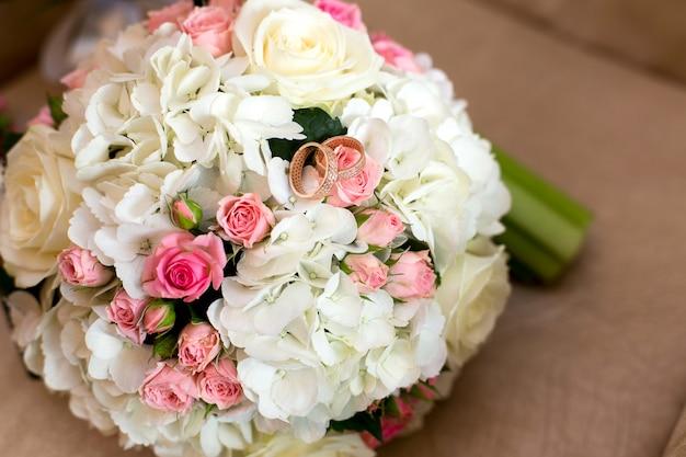 Deux alliances à un bouquet de roses rouges et blanches Photo Premium