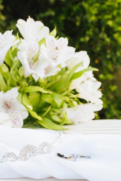 Deux Alliances Et Couronne Sur Foulard Avec Bouquet De Fleurs Magnifique Sur La Table Photo gratuit