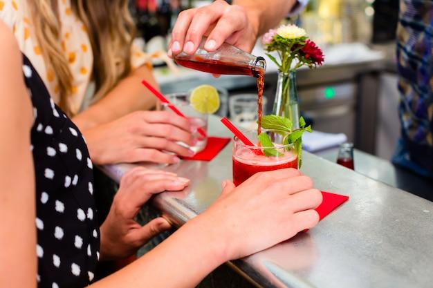 Deux amies au café bar buvant un long drink Photo Premium