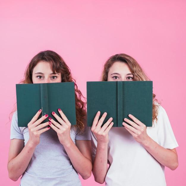 Deux Amies Couvrant Leur Visage Avec Un Livre De Couverture