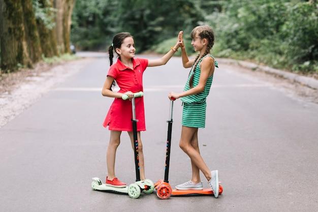 Deux amies debout sur un scooter donnant cinq geste haut sur la route Photo gratuit