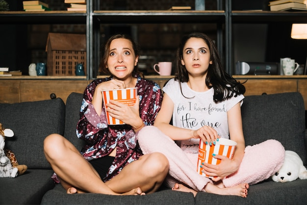 Deux amies effrayées regardant un film d'horreur Photo gratuit