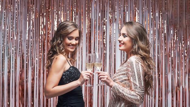 Deux Amies élégantes En Robe De Soirée Discutant Et Buvant Du Champagne. Photo Premium