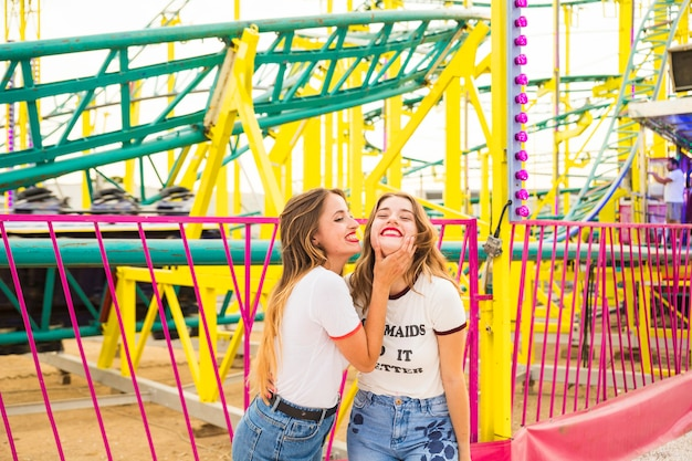 Deux amies heureux debout devant des montagnes russes Photo gratuit