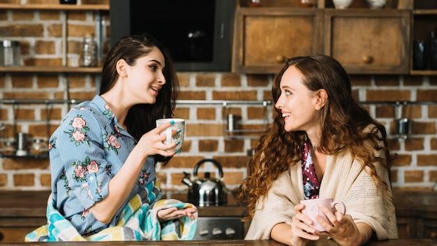 Deux amies joyeuses dégustant une tasse de café Photo gratuit