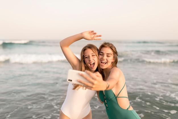 Deux amies joyeuses prenant selfie devant les vagues de la mer Photo gratuit