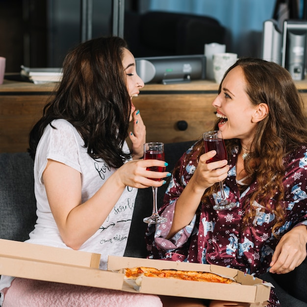 Deux amies qui rient avec des boissons et des pizzas Photo gratuit