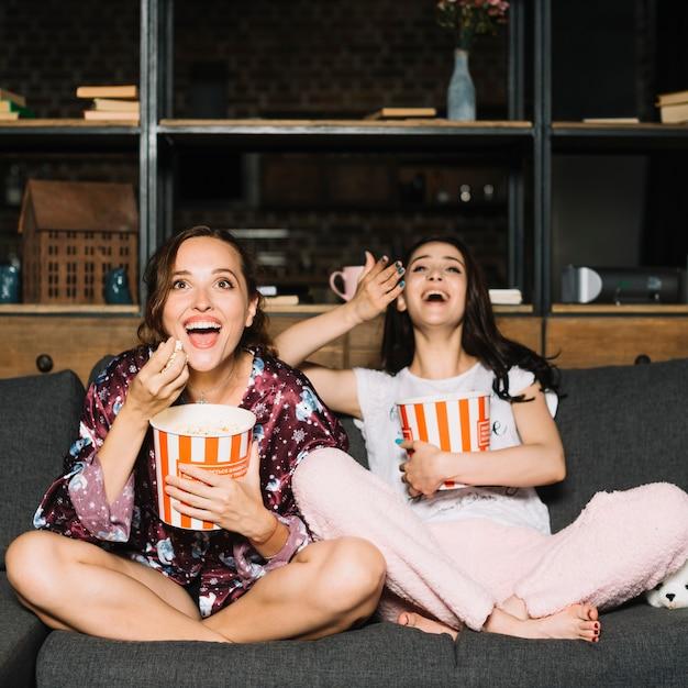 Deux amies rient en regardant un film de comédie Photo gratuit