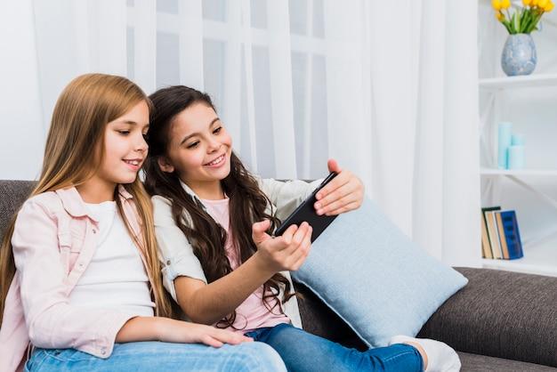 Deux amies souriantes prenant selfie sur téléphone portable à la maison Photo gratuit