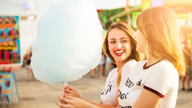 Deux amies souriantes tenant la barbe à papa bleue Photo gratuit