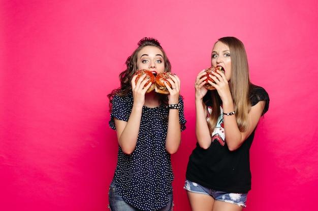 Deux Amis Affamés Avec Des Hamburgers Sur Rose Vif Photo Premium