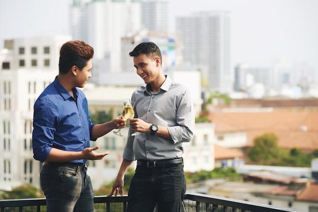 Deux amis asiatiques de sexe masculin discutant et dégustant du champagne lors d'une fête urbaine sur le toit Photo gratuit