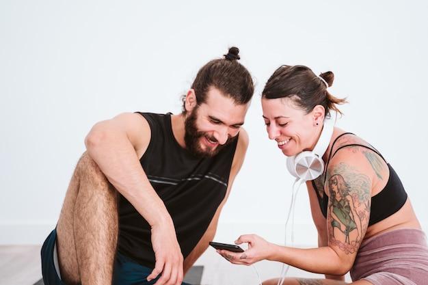 Deux Amis Au Gymnase écoutant De La Musique Sur Un Téléphone Mobile Et Un Casque Et S'amusant Photo Premium