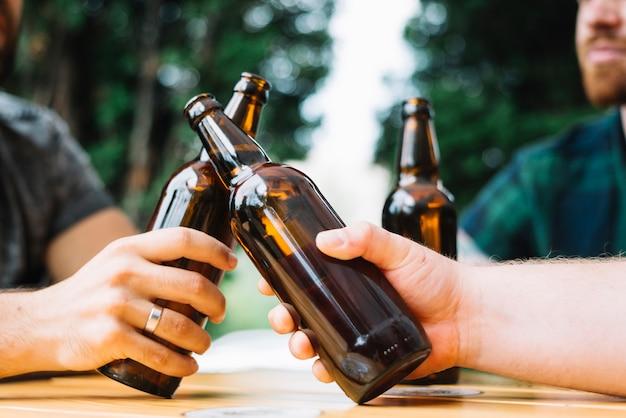 Deux amis claquent les bouteilles de bière sur la table Photo gratuit