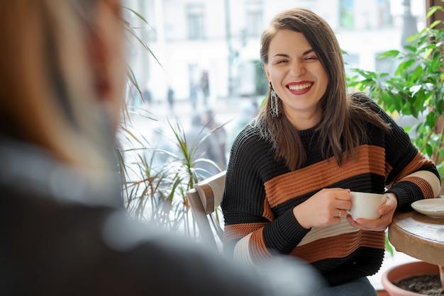 Deux amis dans un café près de la fenêtre Photo Premium