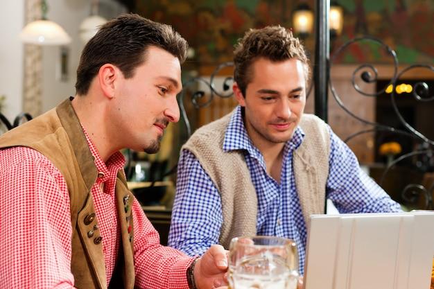 Deux amis dans un pub bavarois avec un ordinateur portable Photo Premium