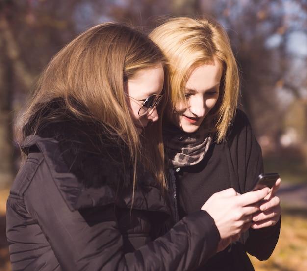 Deux amis femmes heureux partageant les médias sociaux dans un téléphone intelligent à l'extérieur dans un parc Photo Premium