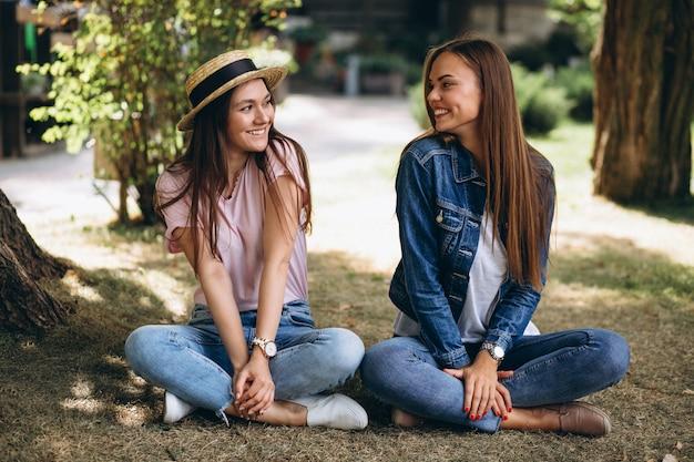 Deux amis filles assis dans un parc Photo gratuit
